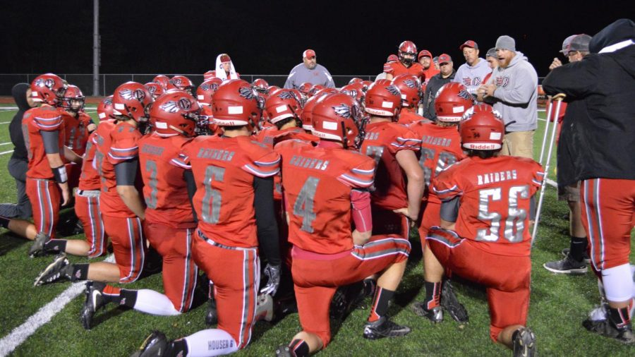 The football Team in a Huddle on Homecoming Night.