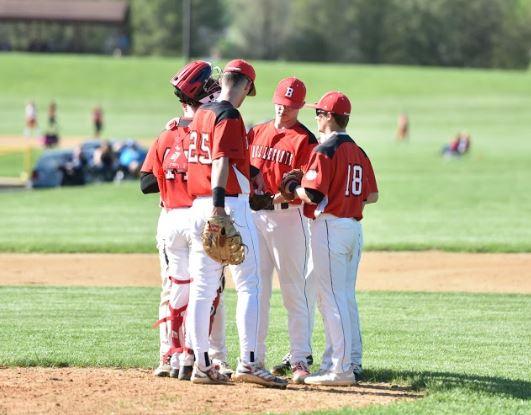 Varsity baseball members in a huddle during the regular spring season.