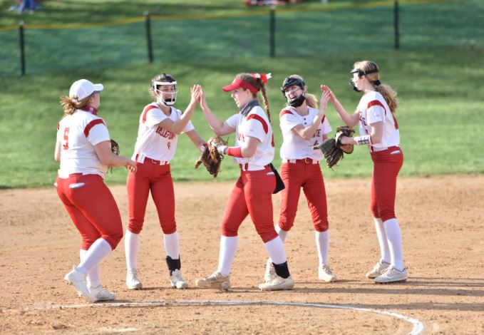 The softball players offer each other encouragement during a game.