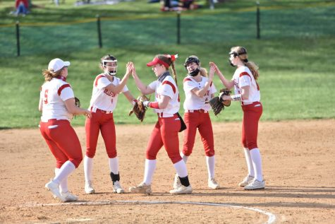 The softball team players on the field during a spring game.