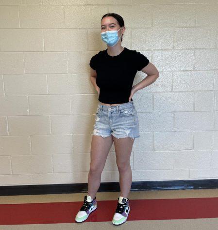 Senior Lia Miner poses in jean shorts and Jordan sneakers.